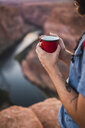 Young man holding red cup - KKAF02856