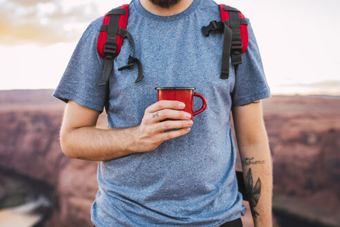 Young man holding red cup - KKAF02859