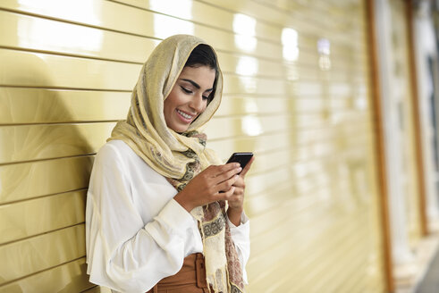 Spain, Granada, young Arab tourist woman wearing hijab, using smartphone - JSMF00547