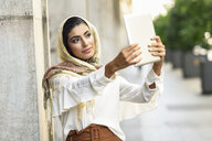 Spain, Granada, young muslim woman wearing hijab using digital tablet computer outdoors - JSMF00550