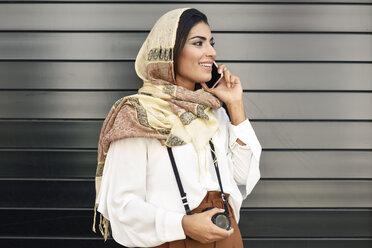 Spain, Granada, young Arab tourist woman wearing hijab, using smartphone - JSMF00553