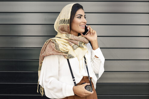 Spain, Granada, young Arab tourist woman wearing hijab, using smartphone - JSMF00553