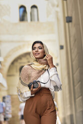 Spain, Granada, young Arab tourist woman wearing hijab, using camera during sightseeing in the city - JSMF00556