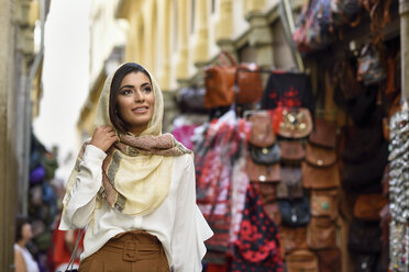 Spain, Granada, young muslim tourist woman wearing hijab during sightseeing in the city - JSMF00559
