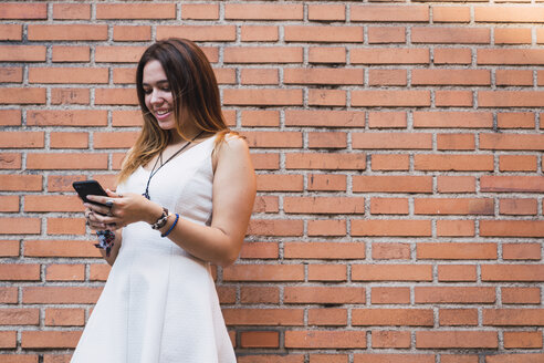 Laughing young woman in front of a brick wall using smartphone - KKAF02879