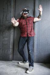 Excited bearded man wearing VR glasses - REAF00462