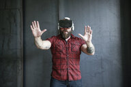 Excited bearded man wearing VR glasses - REAF00465