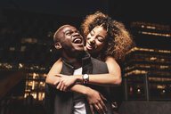 Laughing young couple having fun at night in the city - OCMF00059