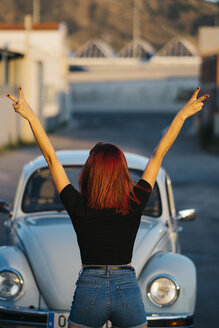 Redheaded woman standing infront of vintage car making victory sign, rear view - OCMF00077
