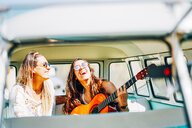 Lesbian couple doing a road trip, singing and laughing in their van - OCMF00080
