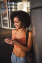 Happy young woman using cell phone - KKAF02887