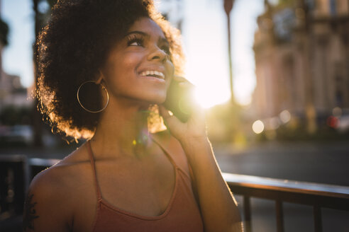 USA, Nevada, Las Vegas, portrait of happy young woman on cell phone in the city - KKAF02899