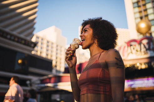 USA, Nevada, Las Vegas, happy young woman eating ice cream in the city - KKAF02902