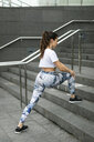 Young woman doing stretching exercise on stairs - FMGF00076