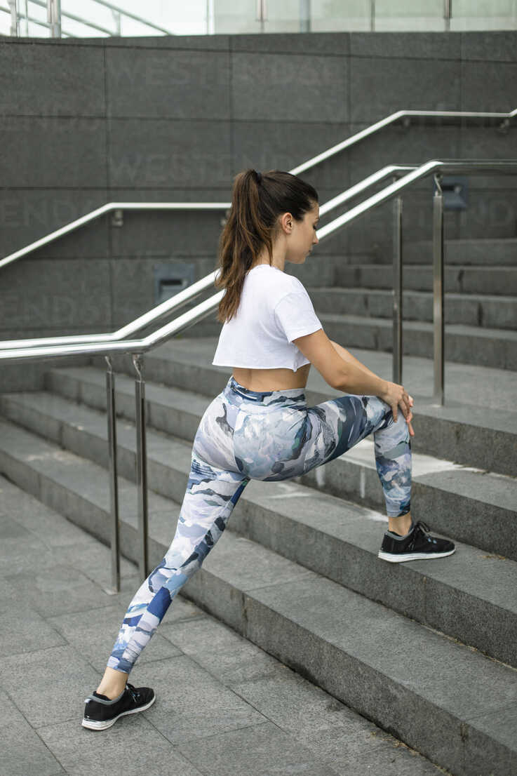 Young woman doing stretching exercise on stairs - FMGF00076 - Nando Martinez/Westend61