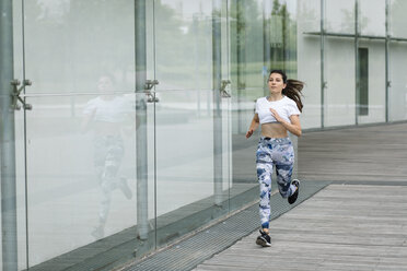 Young woman running along building in the city - FMGF00088