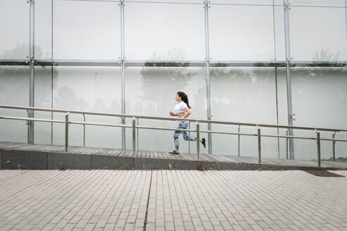 Young woman running along building in the city - FMGF00094