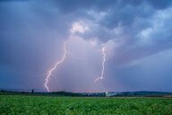 Lightning strikes over a field during a thunderstorm - INGF06176