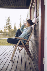 Sweden, Lapland, pensive young woman sitting on chair on veranda looking at distance - RSGF00026