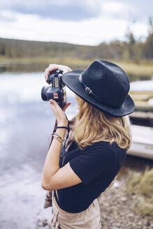 Sweden, Lapland, young woman wearing black hat taking photo with camera - RSGF00035