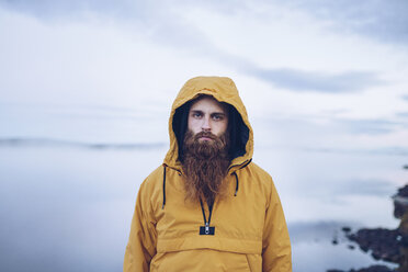 Sweden, Lapland, portrait of serious man with full beard wearing yellow windbreaker - RSGF00044