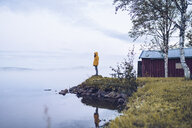 Sweden, Lapland, man wearing  windbreaker standing at water's edge looking at distance - RSGF00047