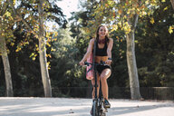 Fit young woman carrying yoga mat, riding bicycle - KKAF02910