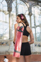 Fit young woman carrying yoga mat, rear view - KKAF02913