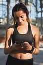 Fit young woman with a smartwatch, using smartphone - KKAF02916