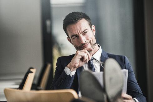 Businessman reading documents, thinking - UUF15777