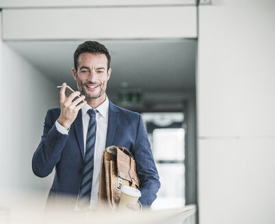 Businessman with briefcase walking in office building, using smartphone - UUF15798