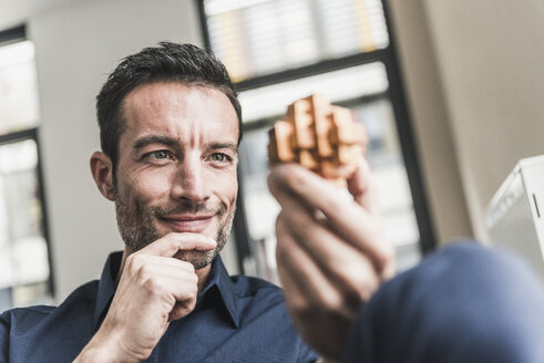 Mature man sitting in office assembling wooden cube puzzle - UUF15813
