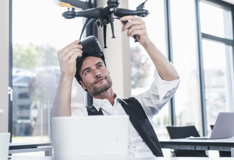 Businessman sitting in office working on a drone, using VR glasses - UUF15855
