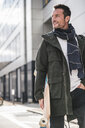Mature man, wearing coat and scarf, walking in the city, carrying longboard - UUF15861