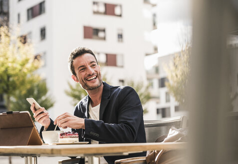 Businessman sitting in cafe, drinking coffee, using smartphone - UUF15876