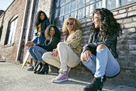 Four young women with curly hair sitting side by side on steps outside a building. - MINF09100