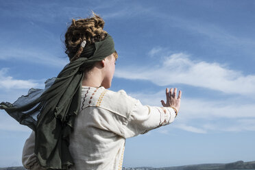 Young woman with brown hair and dreadlocks wearing headscarf standing on a beach , doing Tai Chi. - MINF09163