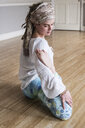 Young woman wearing headscarf and white blouse sitting on floor in yoga pose. - MINF09169