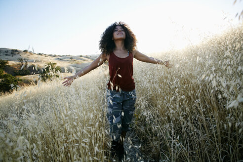 Young woman with curly brown hair hiking in urban park, standing in field, eyes closed. - MINF09184