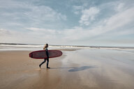 Man in a wetsuit walking towards sea holding a surf board - MINF09391
