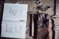 Still life of artisan metalworker's tools, sketches in a notebook and a blackened thick protective glove - MINF09406