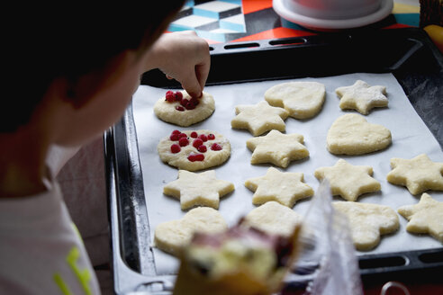 Close-up of boy putting berry fruits on cookie dough at home - CAVF53178