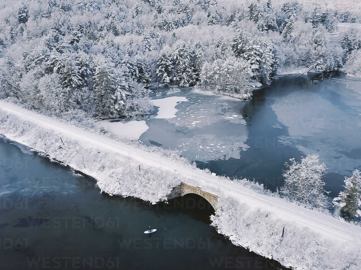 High angle view of person paddleboarding in lake by bridge during winter - CAVF53208 - Cavan Images/Westend61