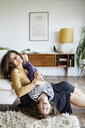 Happy mother holding daughter upside down while sitting on floor by sofa at home - CAVF53220