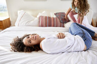 Portrait of happy mother playing with daughter while lying on bed at home - CAVF53235