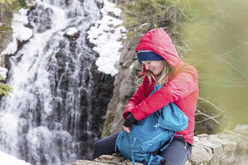 Smiling woman with backpack sitting against waterfall at White Mountains during winter - CAVF53259