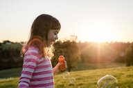 Side view of girl blowing bubbles while standing against clear sky at park during sunset - CAVF53277