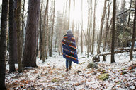 Rear view of woman with blanket walking in forest at Algonquin Provincial Park during winter - CAVF53280