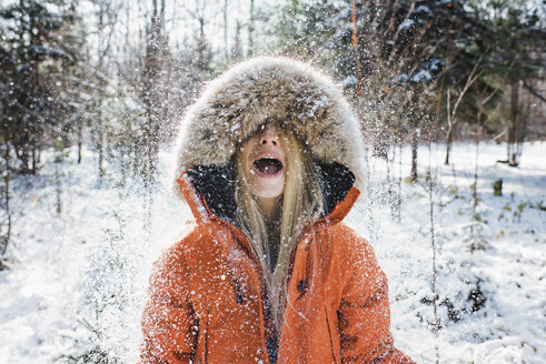 Cheerful woman wearing fur coat while playing with snow in forest at Algonquin Provincial Park - CAVF53283