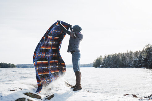 Full length of woman waving blanket while standing on snow covered rocks by lake against clear sky at Algonquin Provincial Park - CAVF53286